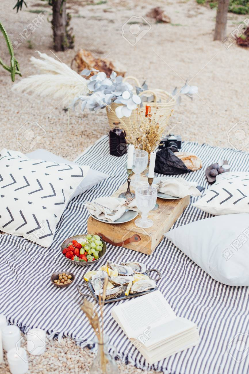 Top view on still life outdoor picnic blanket setup for romantic day or night out for hipster stylish couple, wedding, proposal happening with candles and chic snacks - 86878092