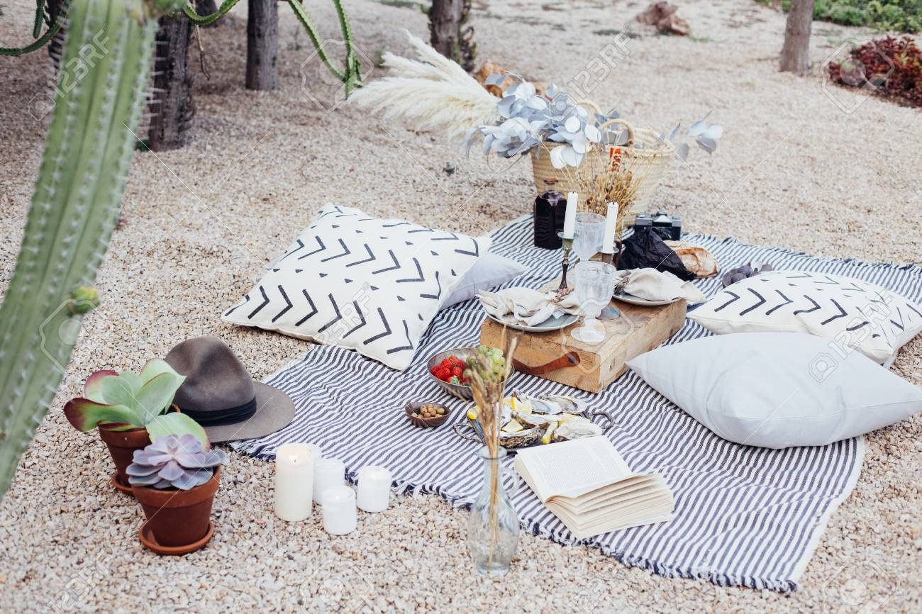 Top view on still life outdoor picnic blanket setup for romantic day or night out for hipster stylish couple, wedding, proposal happening with candles and chic snacks - 86878095
