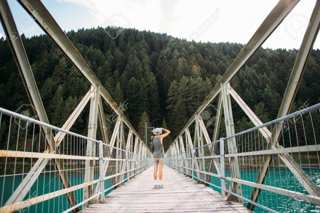 Young fit adventurer man with camera makes photo of nature, stands in middle of metal pedestrian bridge over pristine blue water lake that connects two shores, forest and city - 86878097