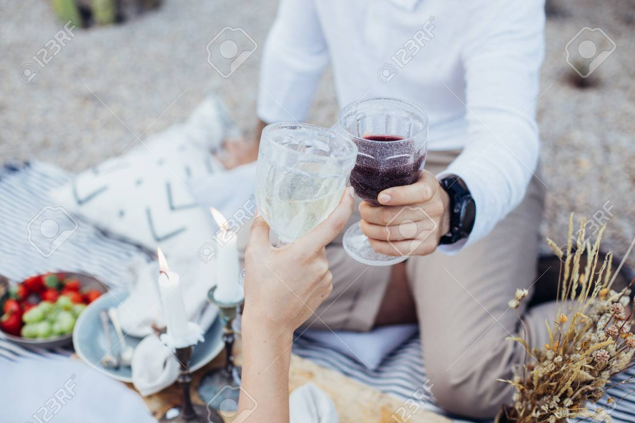 Beautiful people enjoy drinks, red and white wine on picnic date in beautiful setting. Romantic getaway for engagement or proposal, refreshing alcohol beverages - 86878100