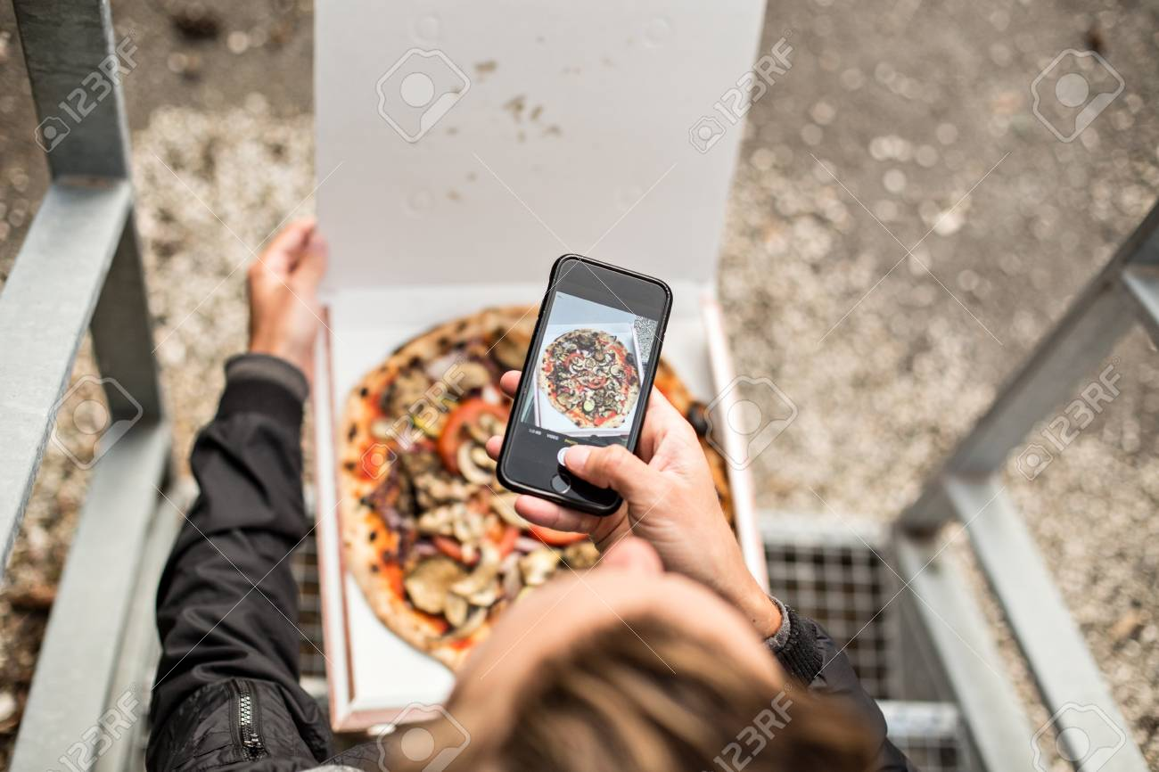Social media influencer millennial hipster makes photo of his fresh hot out of the box delivery take away pizza on his smartphone for sharing online with followers - 86878103