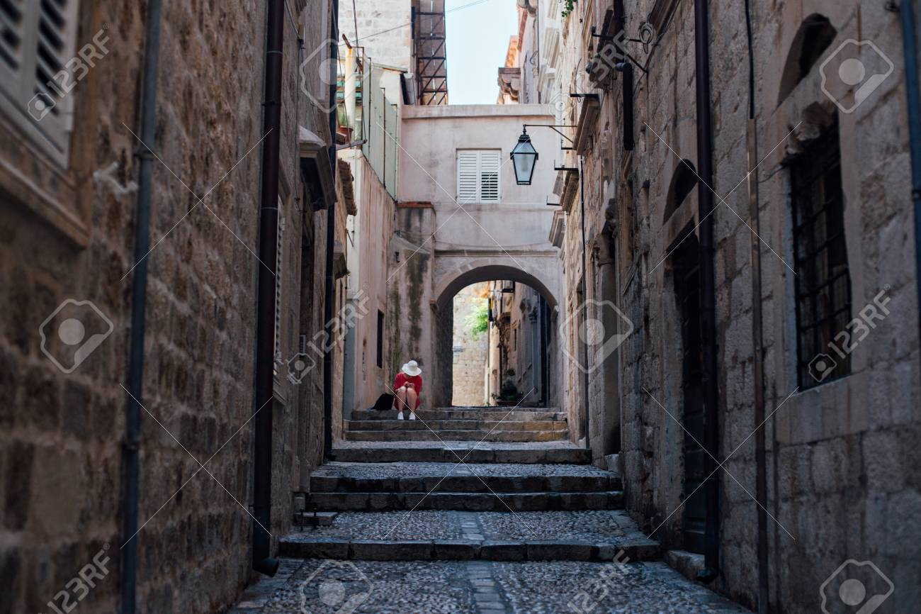 Narrow steep street of beautiful ancient european village or city, Dubrovnik Croatia with cobbled paved walls and floors. Lonely lost tourist sits on steps, exploring - 86878109