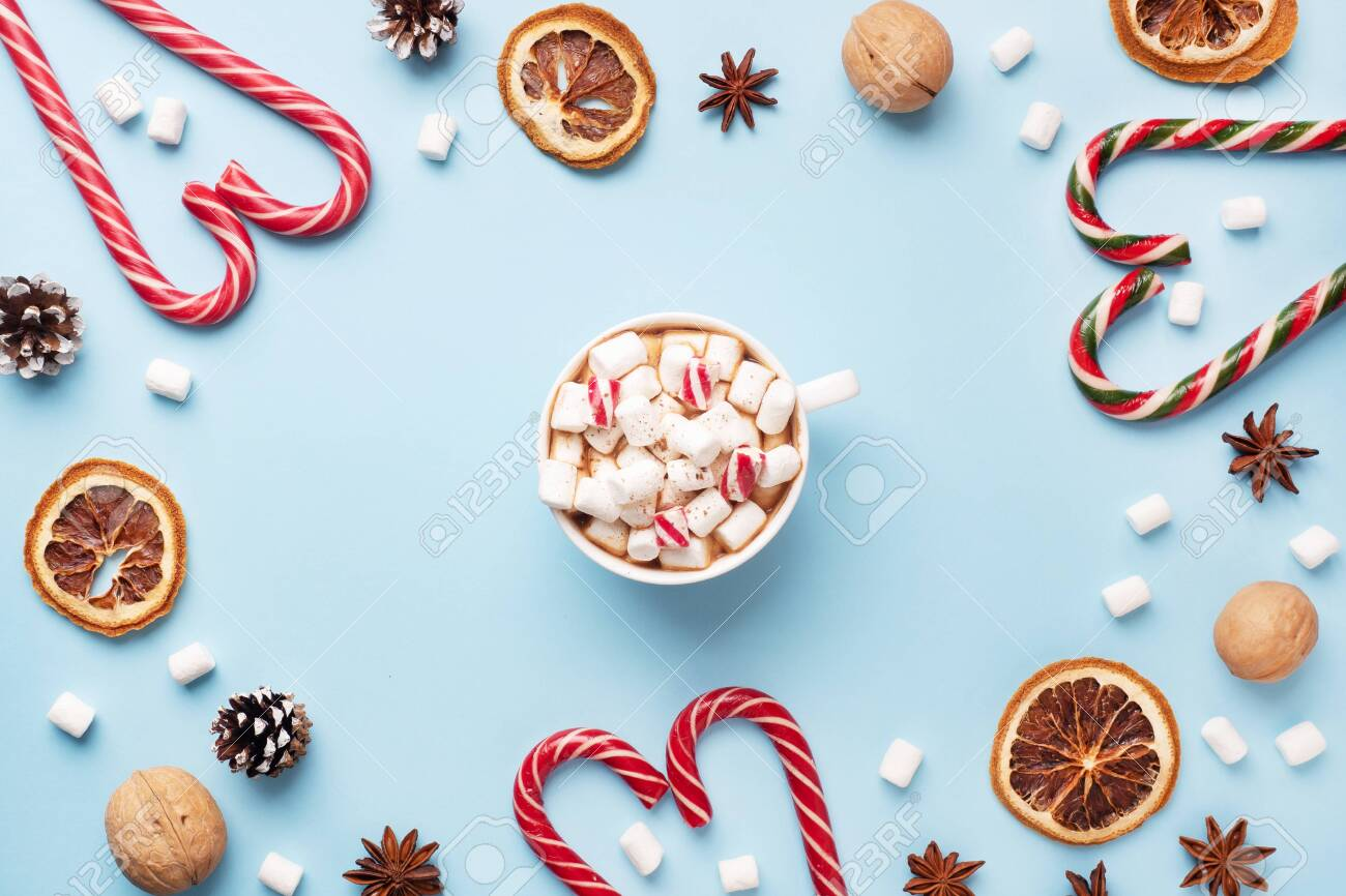 Cup of hot chocolate with marshmallow cocoa powder and caramel nuts, oranges on pastel blue background with copy space. Christmas winter concept - 135477429