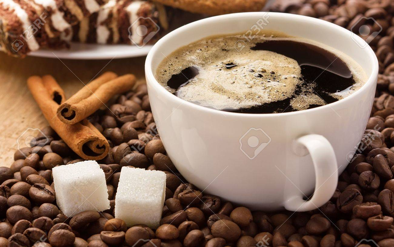 Coffee cup, cinnamon and sugar cubes on coffee beans, sweets on the background Stock Photo - 14119724