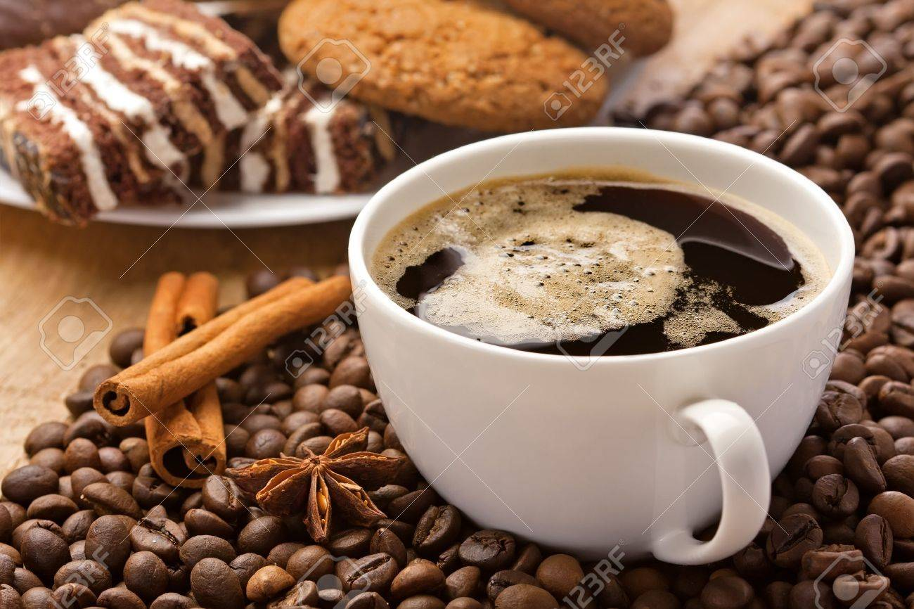 Coffee cup, cinnamon, anise on coffee beans, sweets on the background Stock Photo - 17721579