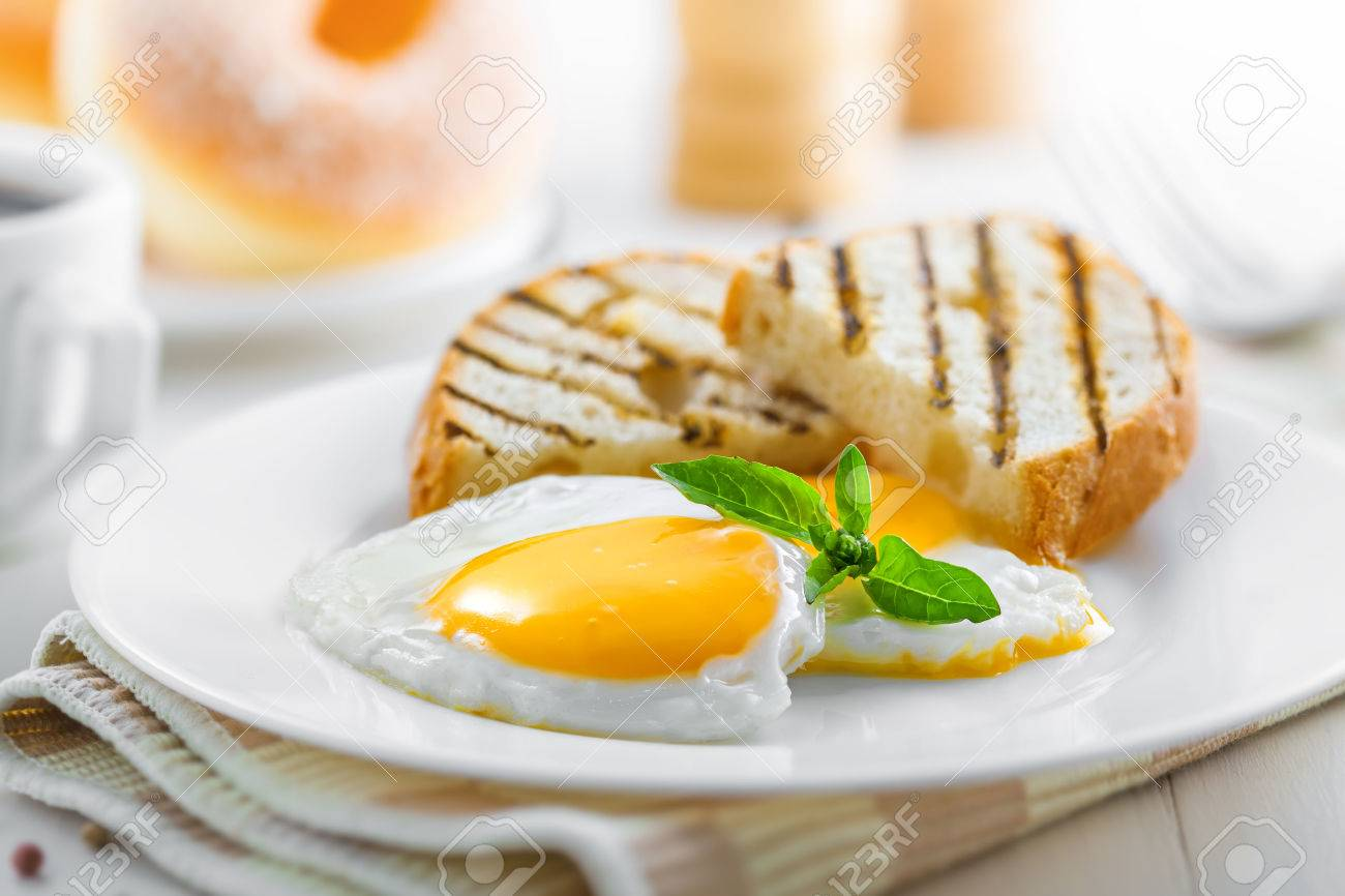 Fried eggs with toasts, coffee and donuts, traditional breakfast, close-up Stock Photo - 47214434