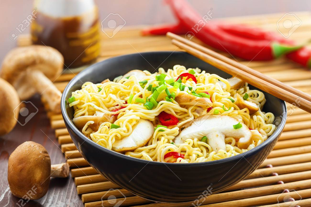 Instant noodles with shiitake mushrooms, pepper and onion in a bowl, Asian meal on a table - 54869537