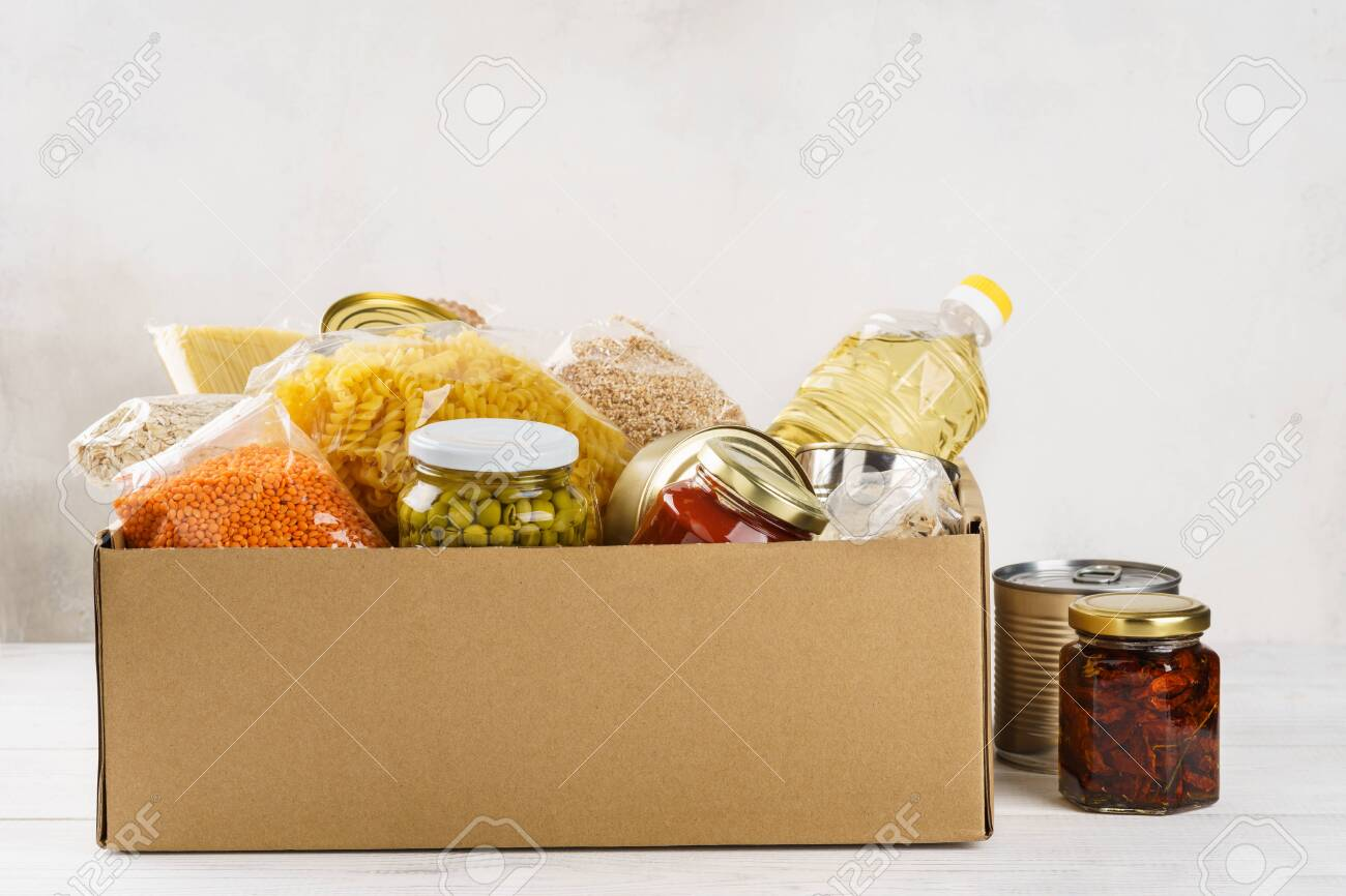 Various canned food, pasta and cereals in a cardboard box. Food donations or food delivery concept. - 126798569