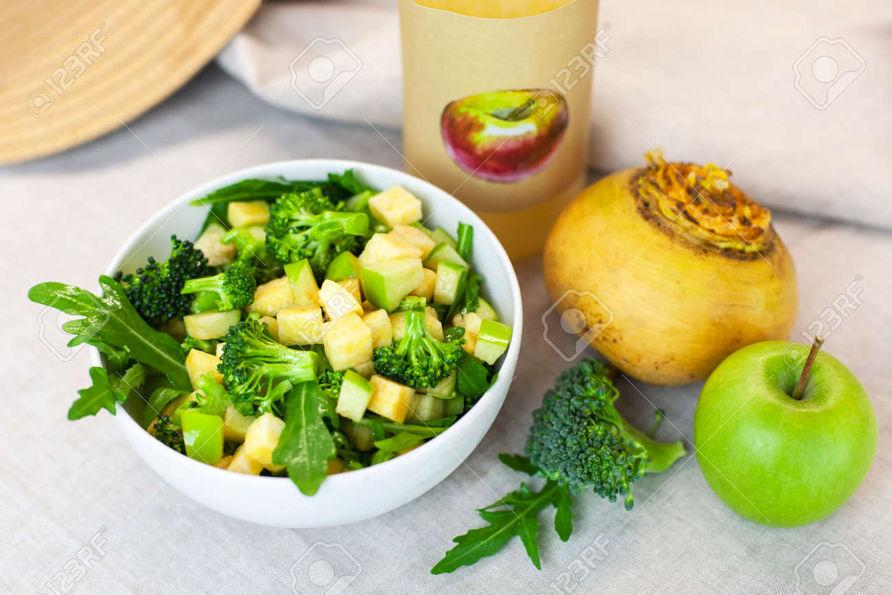 Fresh spring green vegetable salad on a table with apples, turnips, arugula, broccoli on a light background. Farm organic product, home-made. - 141091703