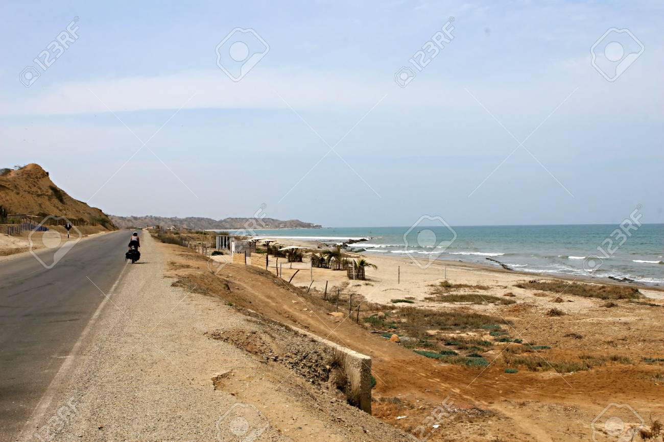 A cyclist travels down the road along the ocean in Peru Stock Photo - 4057892
