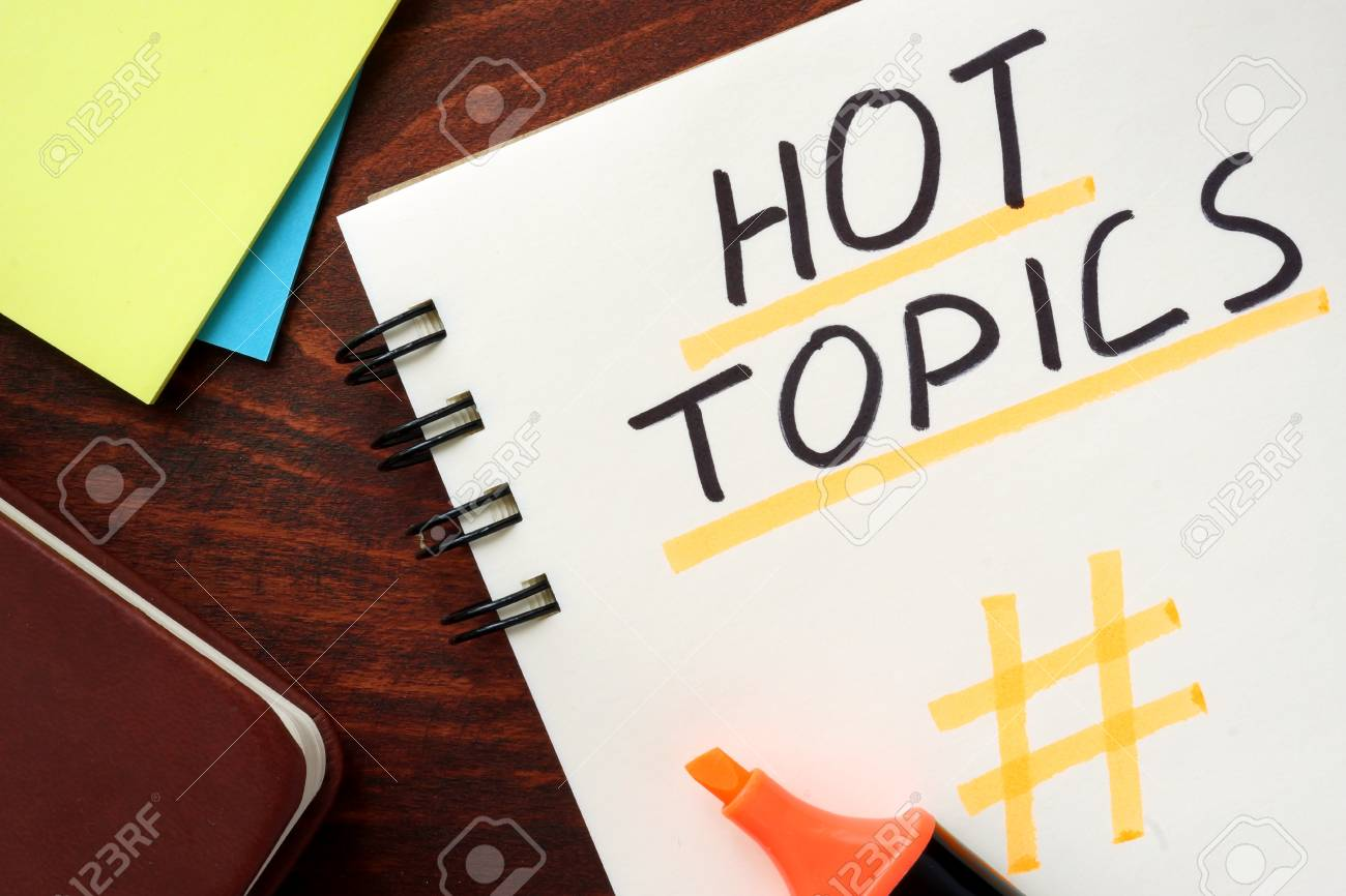Hot Topics written in a notepad on a wooden background. - 56029651