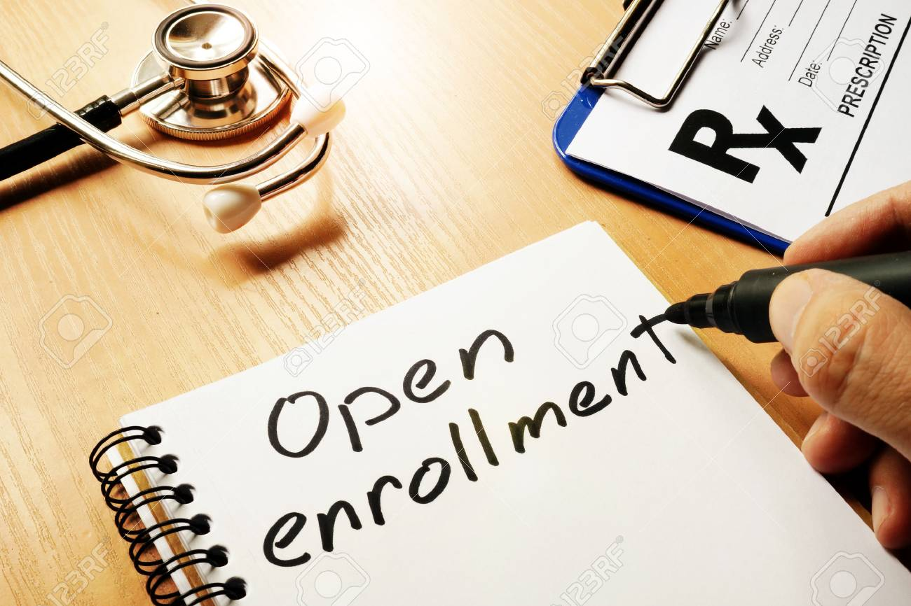 Open enrollment written on a note and medical stethoscope. - 80203753