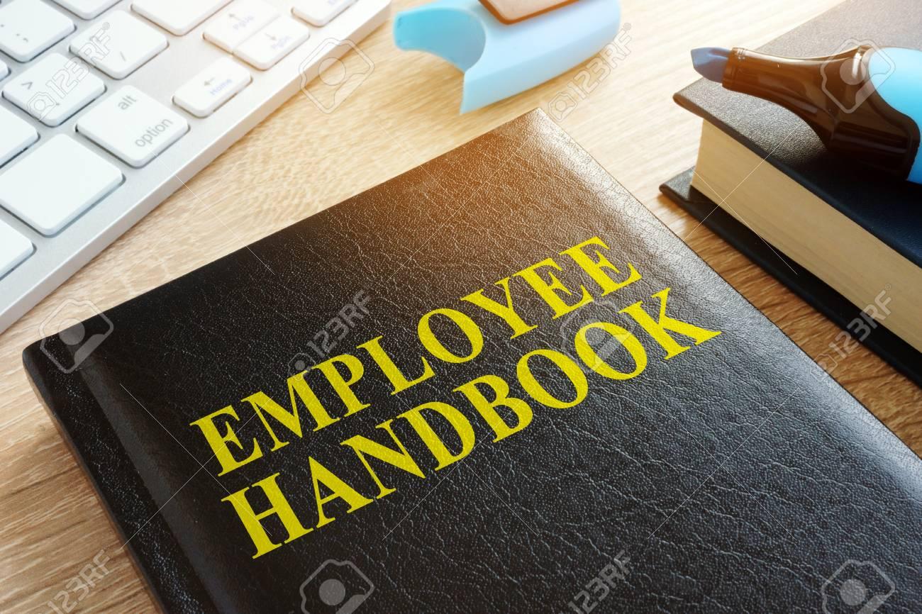 Employee handbook on a wooden desk. - 94919801