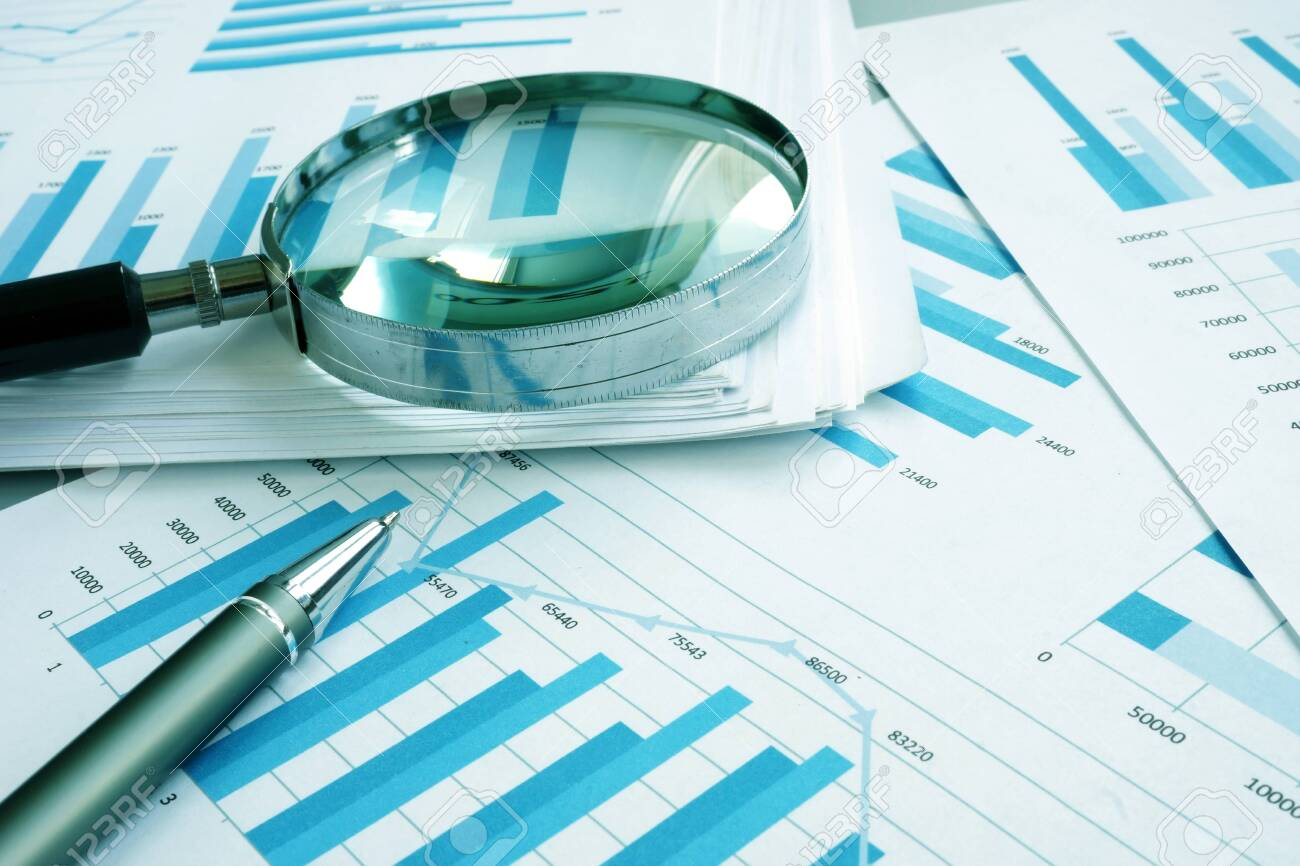Assessment and audit. Business papers with financial charts and Magnifying glass. - 124399625