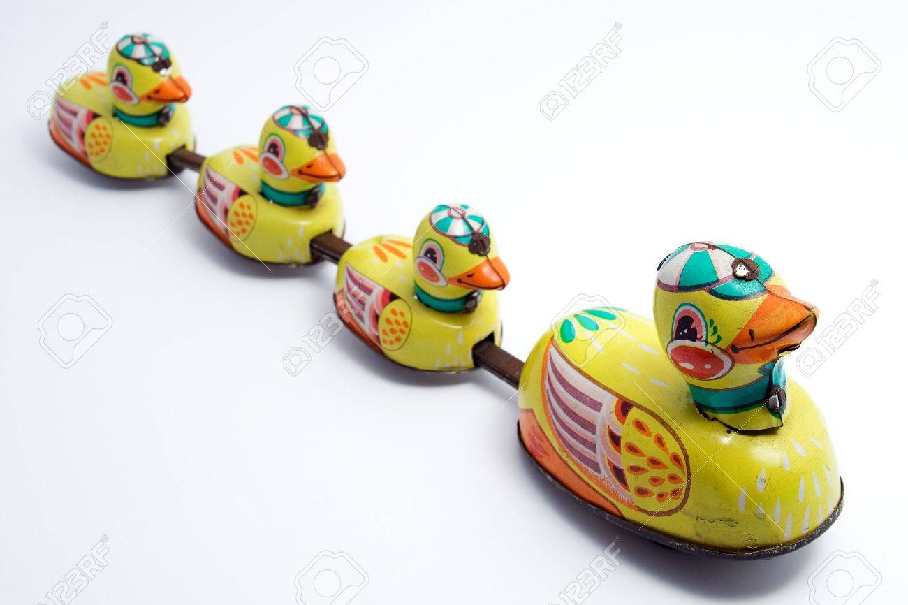 an old windup tin toy of one duck and three ducklings in a line
