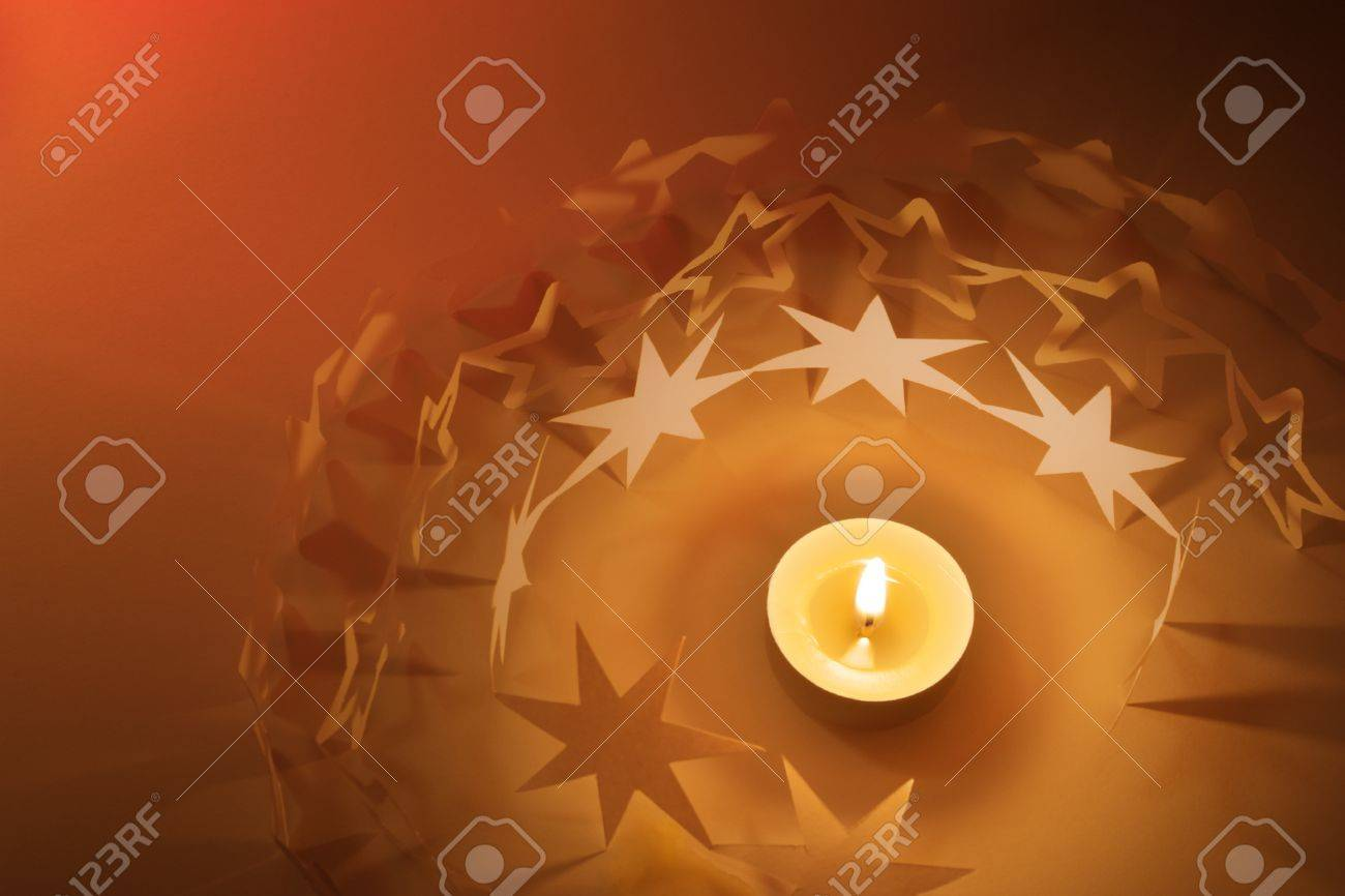 Children made star paper chains around a candle, with a red background light Stock Photo - 13147180