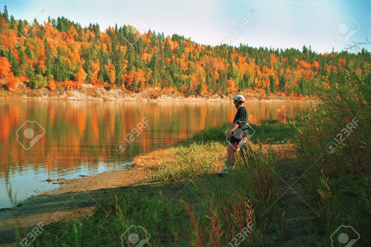 Cyclist taking a break by river in autumn Stock Photo - 6212911