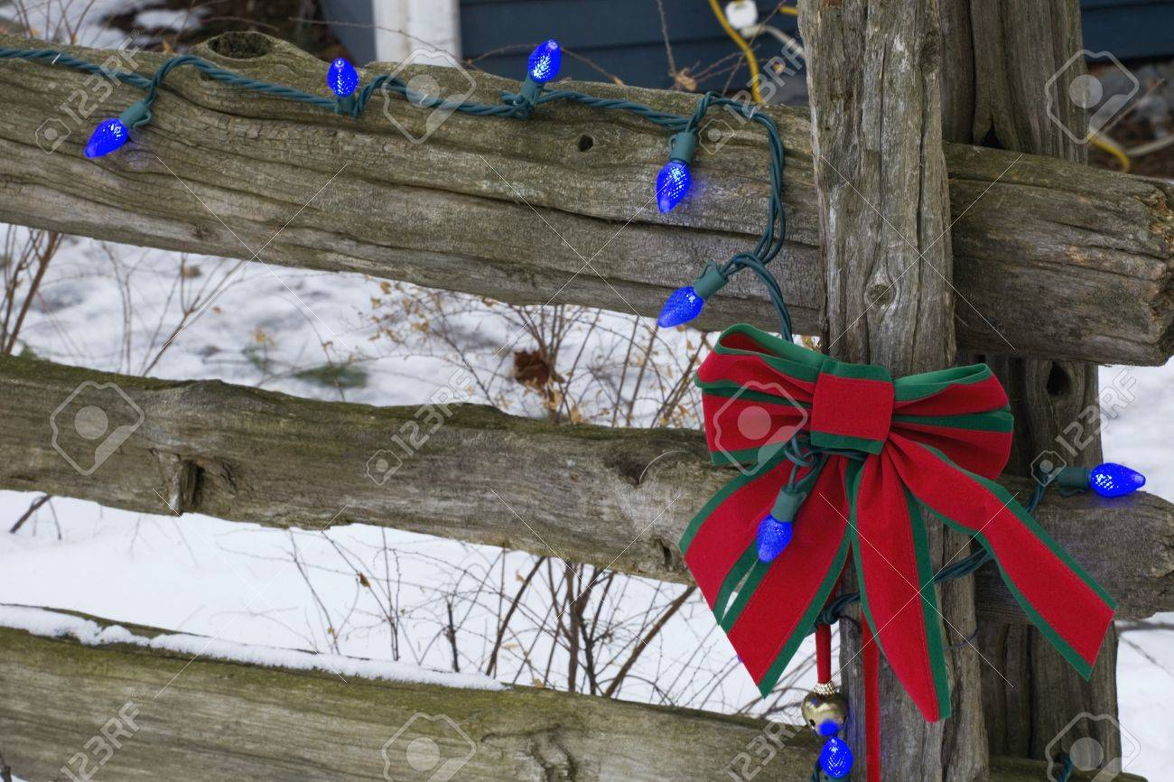 christmas decorations on an old wooden fence outside in the snow stock photo 7268369
