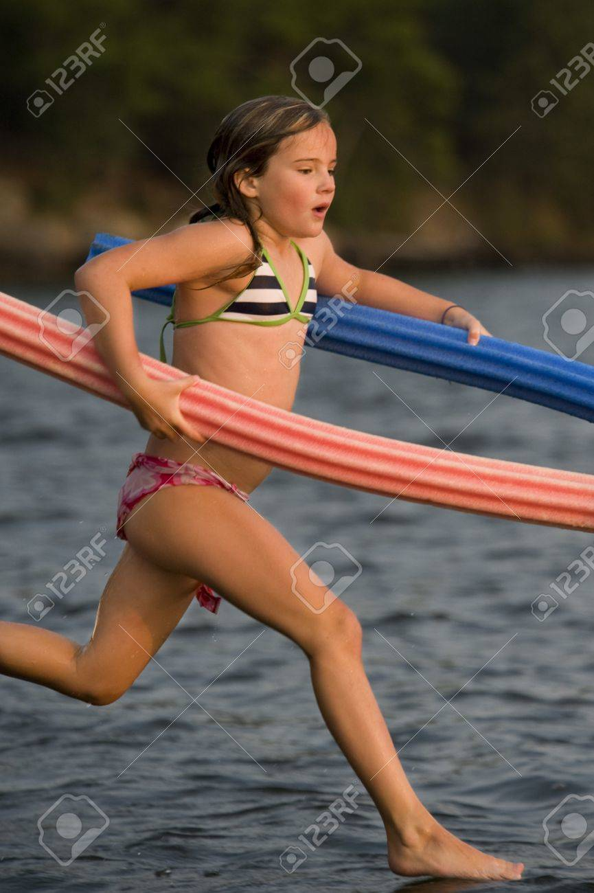 Young girl running with pool toys, Lake of the Woods, Ontario, Canada Stock Photo - 7191458