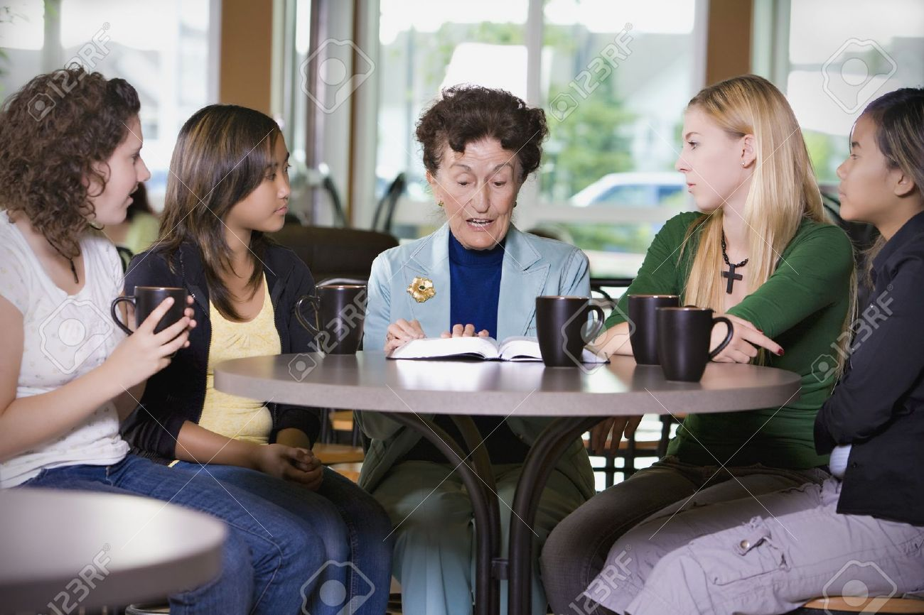 Group of girls listening to senior woman in restaurant Stock Photo - 7192964