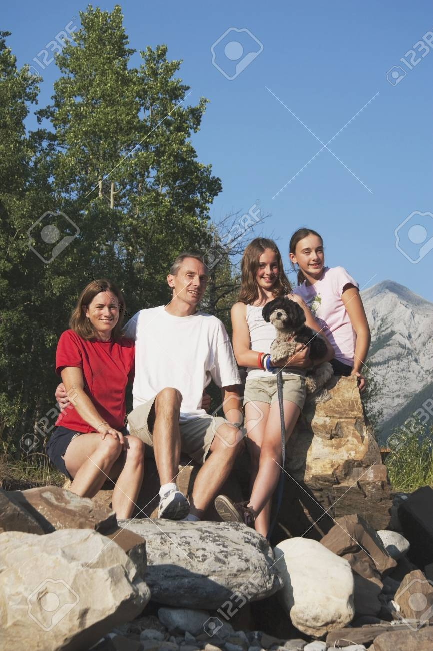 kananaskis country, alberta, canada; a family sitting on the rocks in the mountains with their dog Stock Photo - 7190704