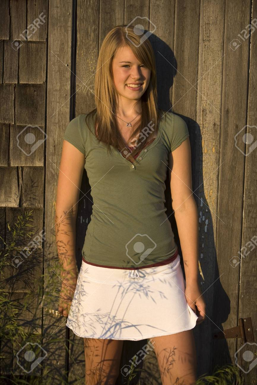 Young woman standing against old wooden building Stock Photo - 7191489