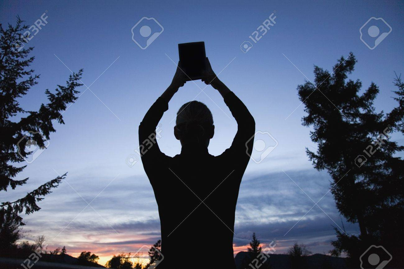 Silhouette of a Bible raised to the heavens Stock Photo - 7192000