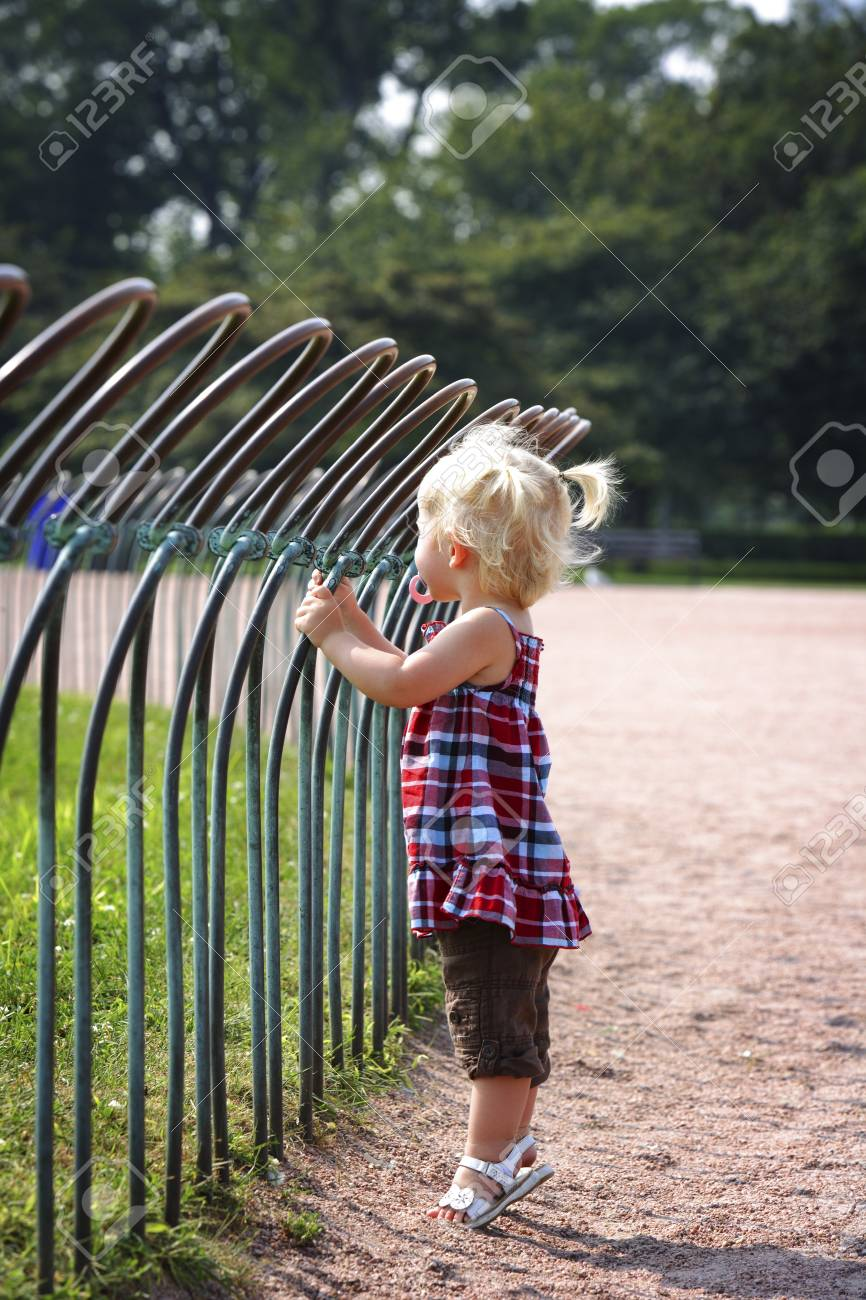 Girl standing against a fence in a park Stock Photo - 7208952