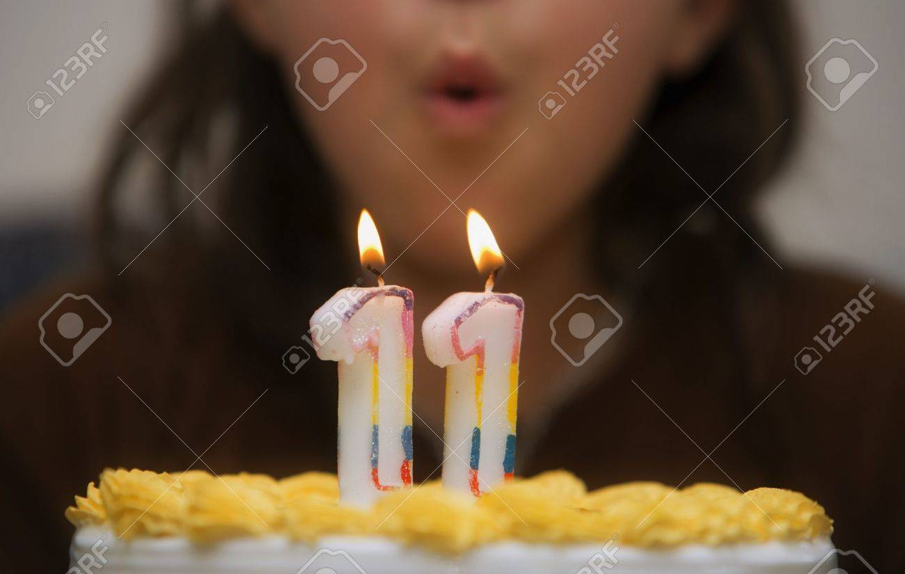 Girl Blowing Out Candles On A Birthday Cake Stock Photo Picture And