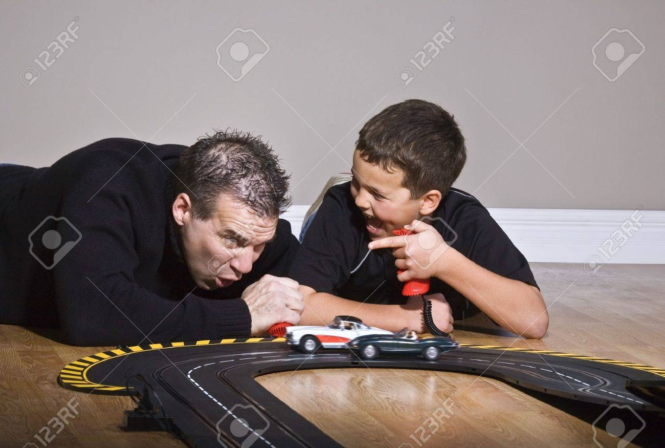 Father and son playing with race track Stock Photo - 7208821