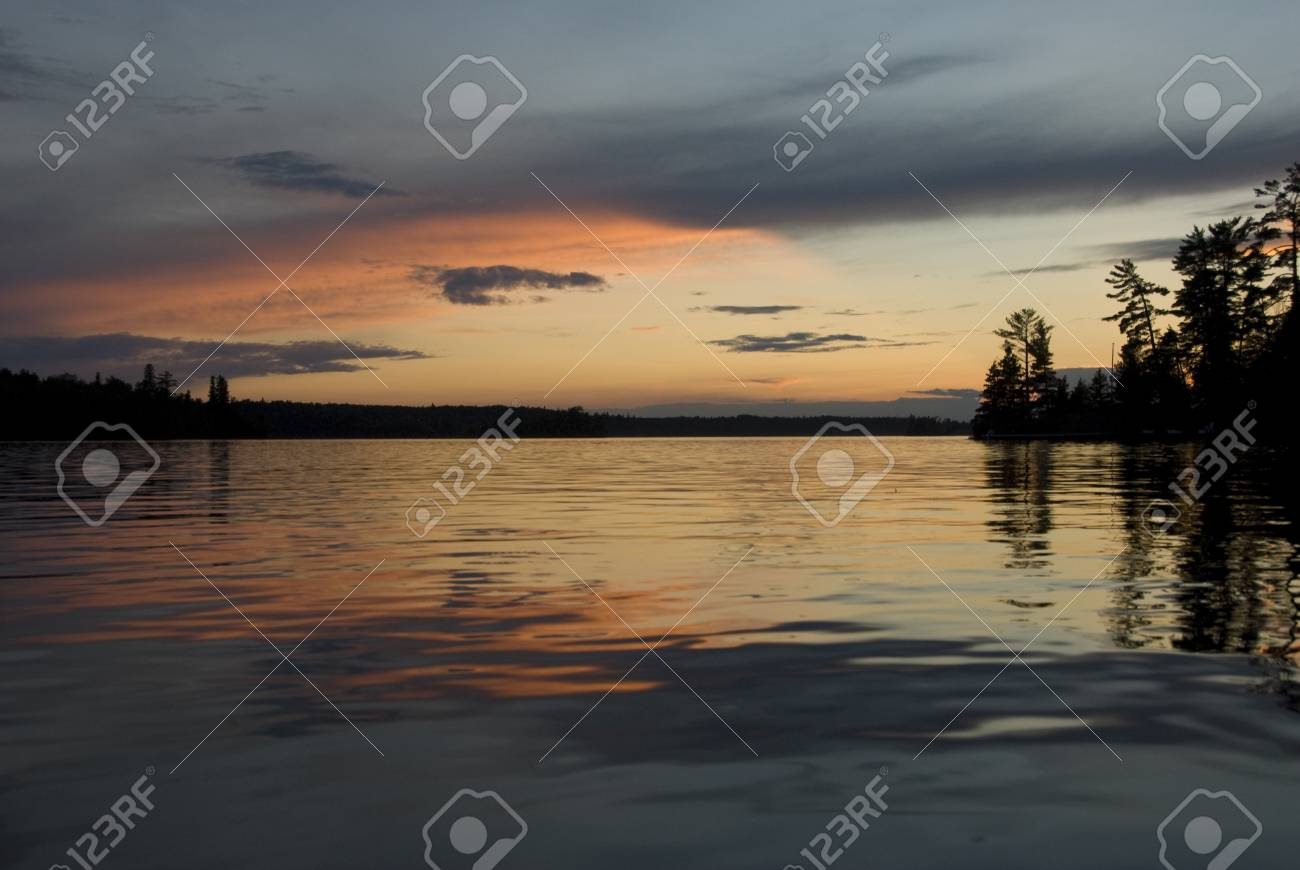Lake of the Woods, Ontario, Canada; Reflection of majestic sunset in placid lake Stock Photo - 7551657