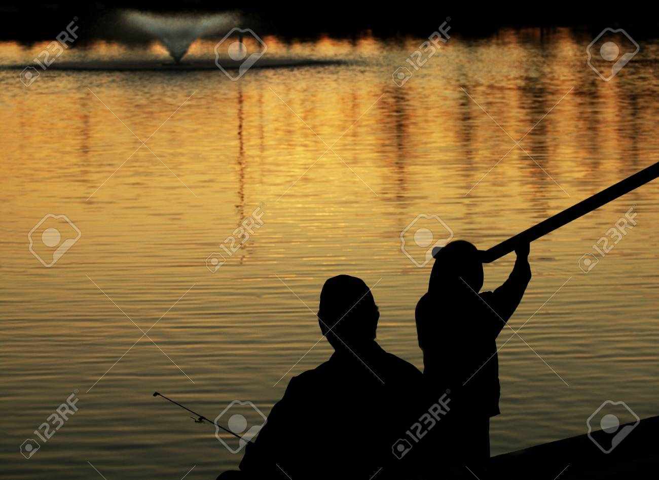 Silhouette of adult and child fishing Stock Photo - 7551692