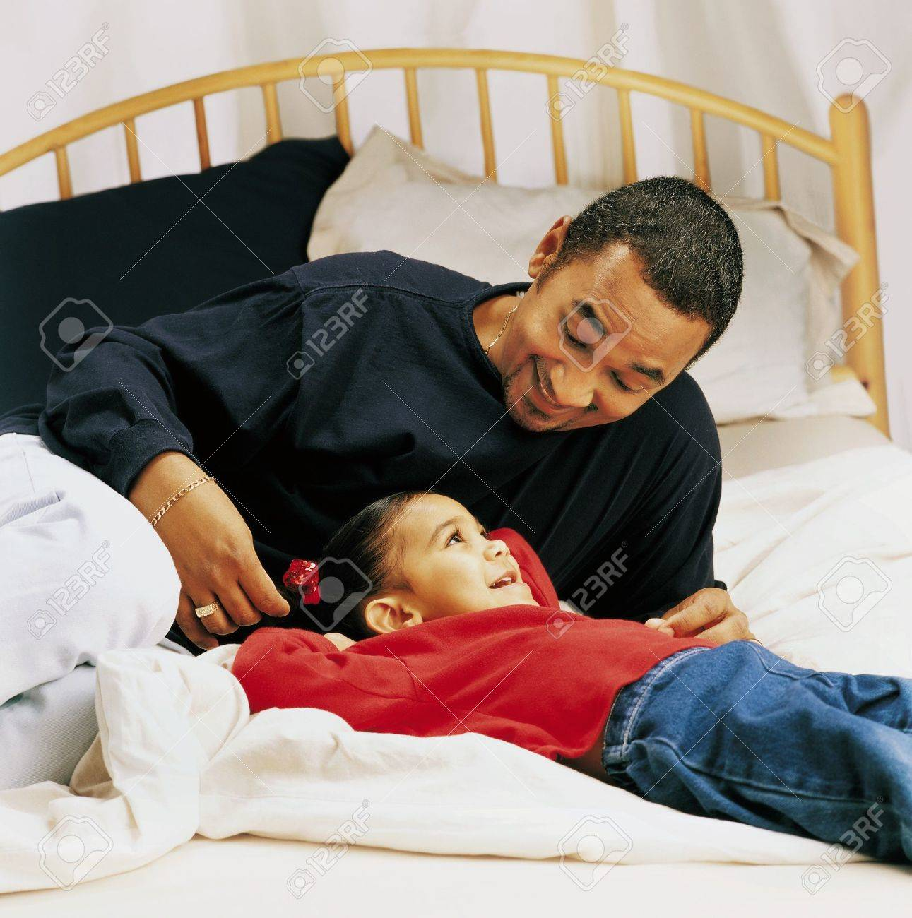 Father and little girl talking on a bed Stock Photo - 7559365