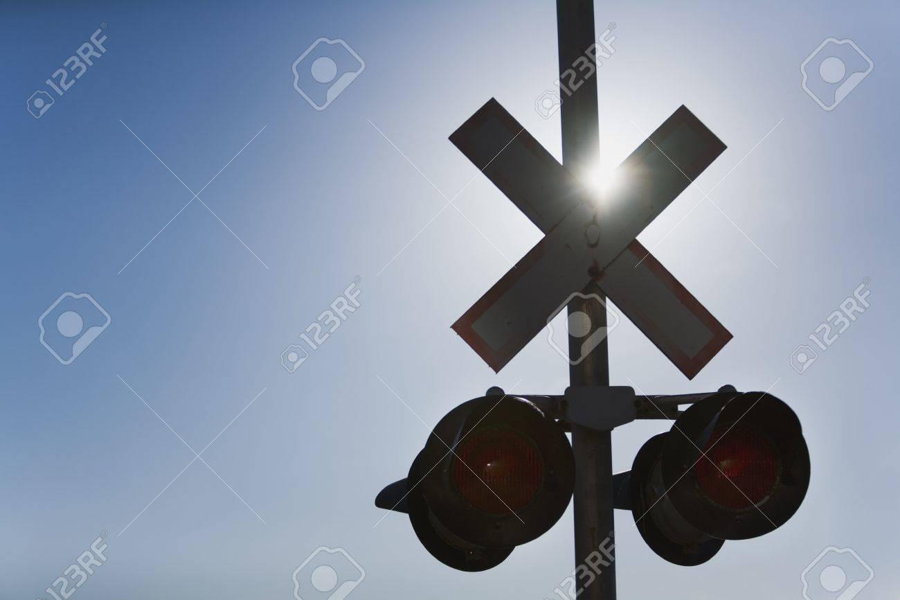 Railroad crossing lights with sun glare
