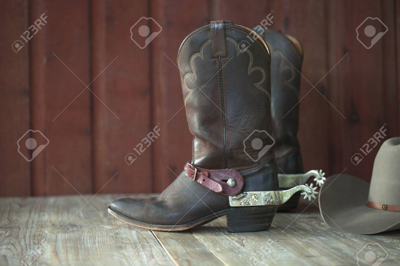 Cowboy boots with spurs and a hat on an old wood