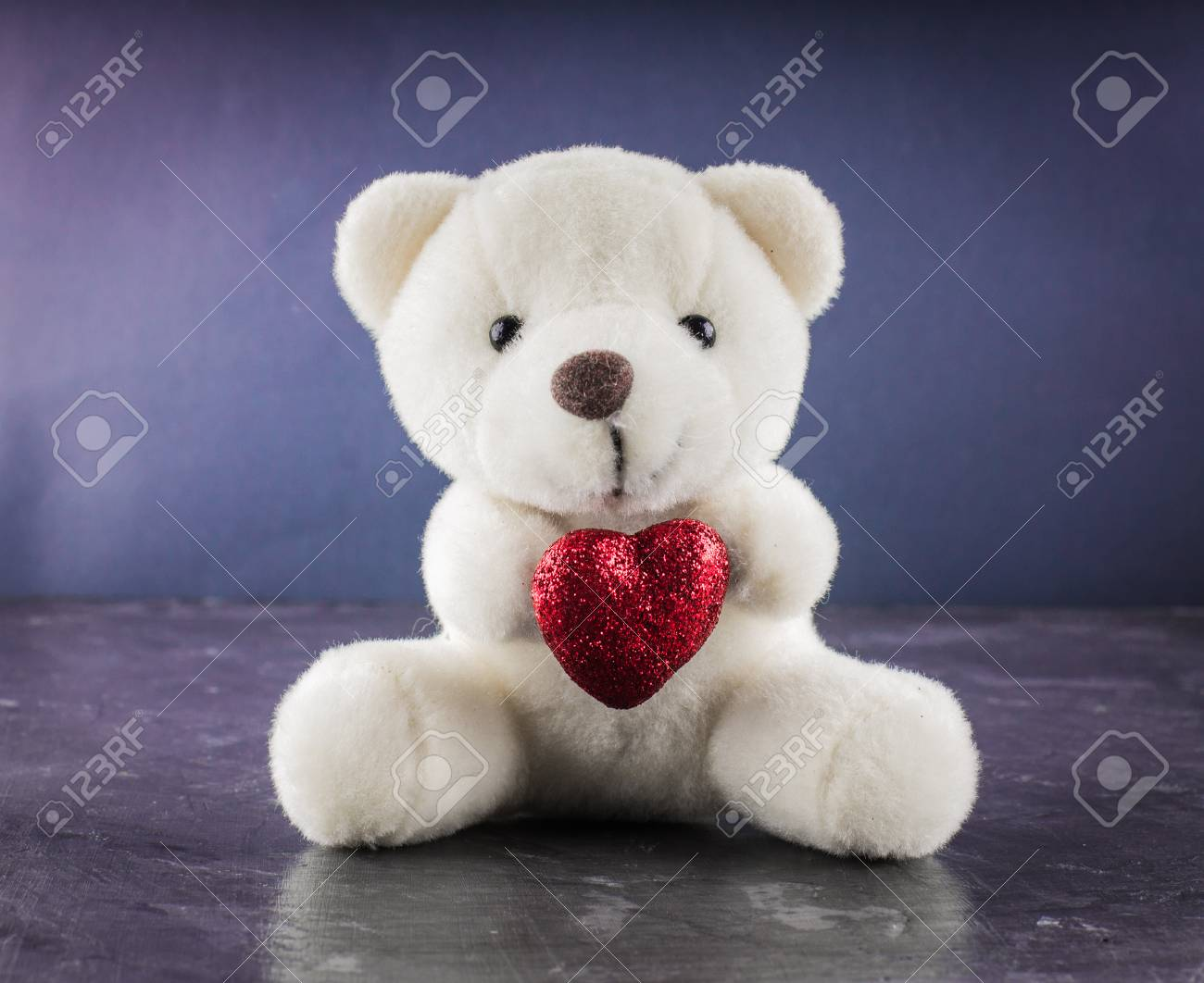 white teddy bear with love letter on red heart on gray background