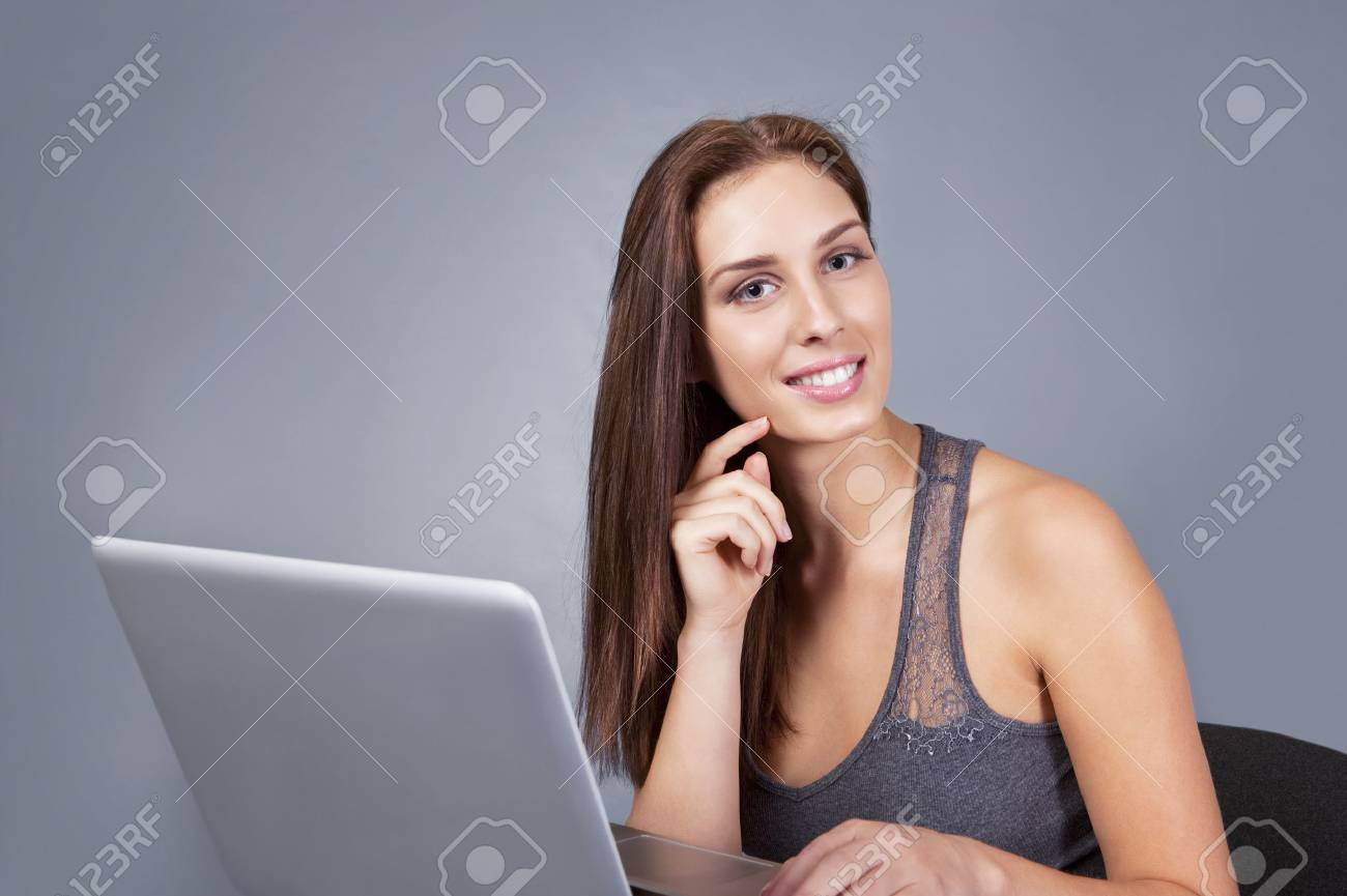 Smiling young woman with laptop looking up Stock Photo - 12622407