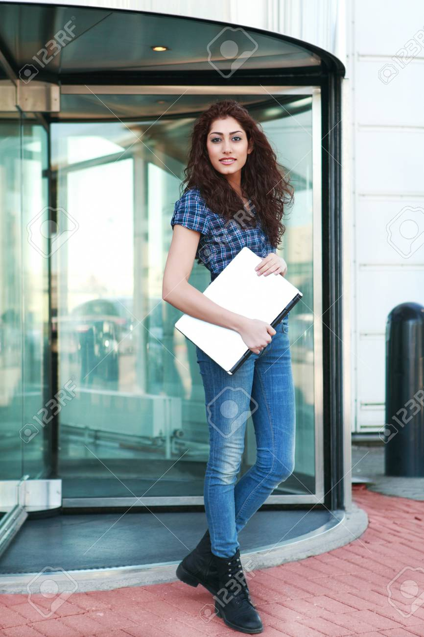 Smart young woman leaving an office building Stock Photo - 12908521