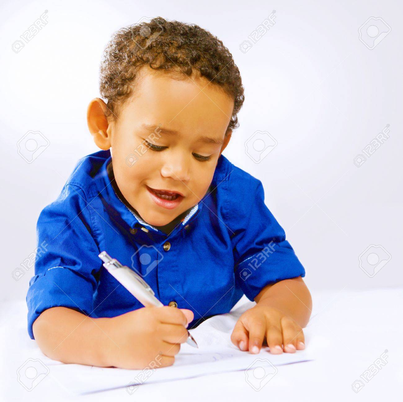 cute kid writing or doodling with pen on paper stock photo, picture