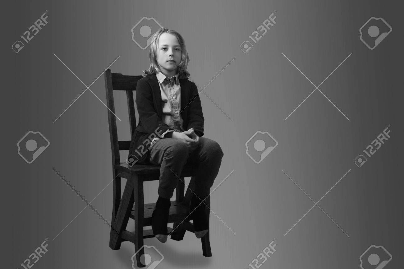 Black child sitting in chair - Sad Lonely Child Sitting In Chair Stock Photo 29052202