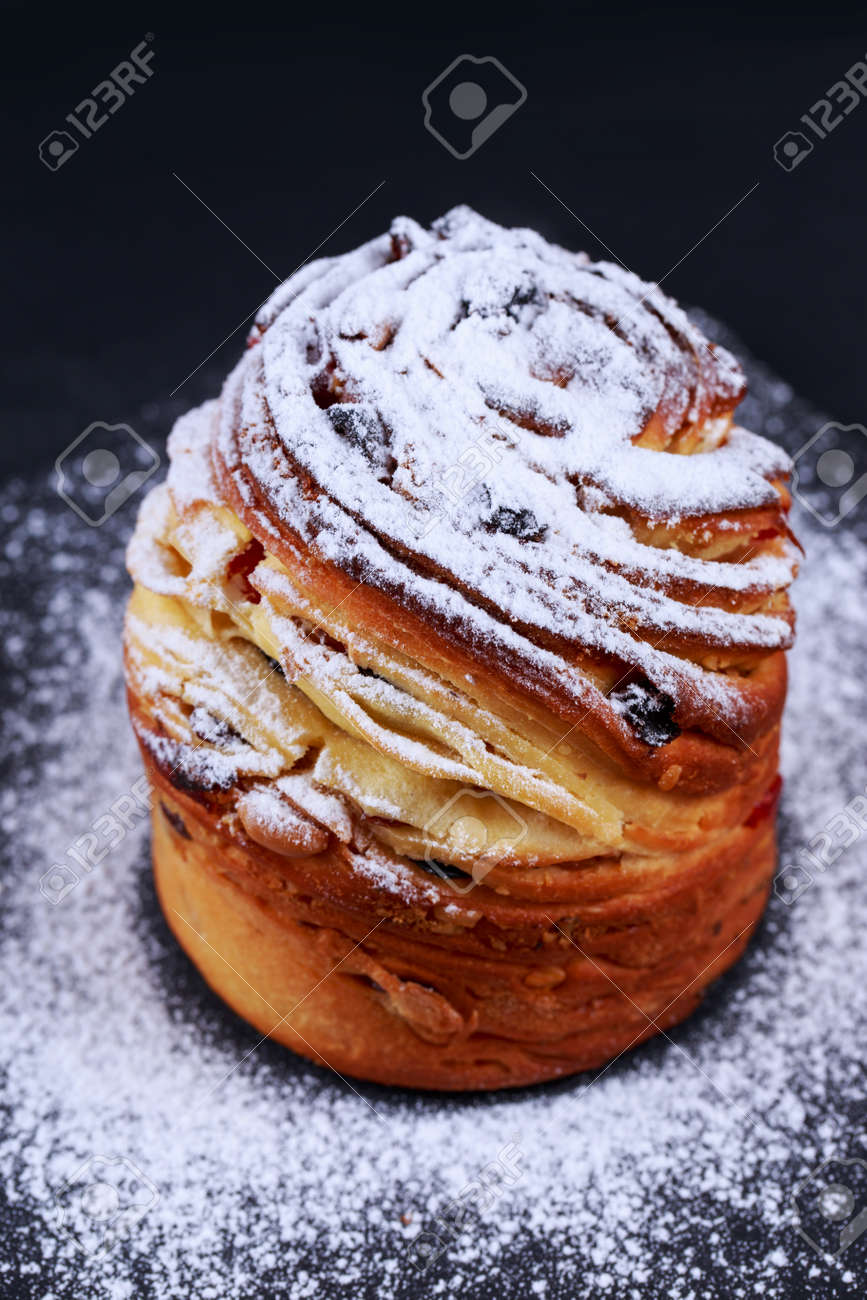 Large kraffin with raisins and powdered sugar on a gray background - 155944417