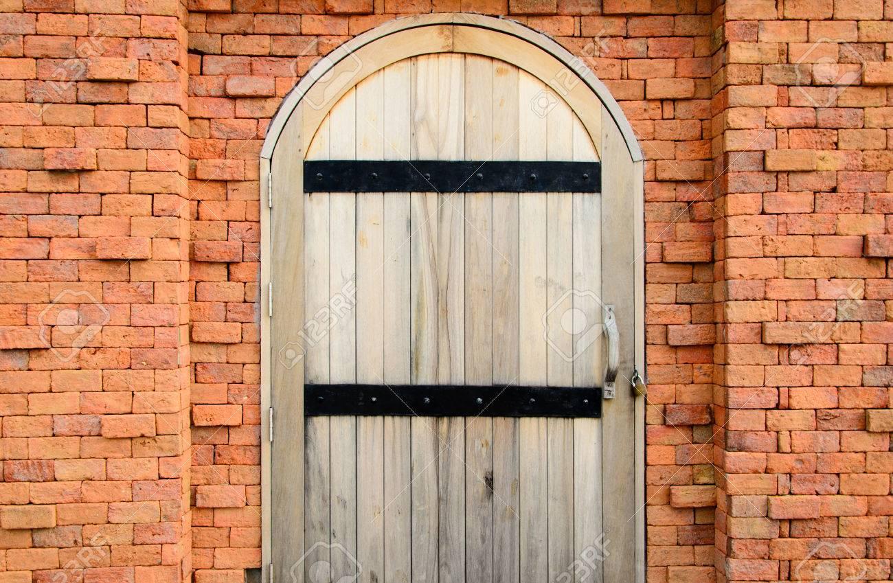 Stock Photo   Vintage Wood Door With Lock On Orange Brick Wall
