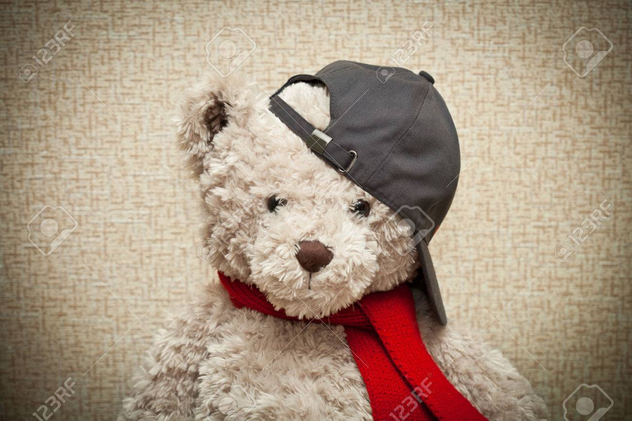 Stock Photo - Teddy bear in a red scarf and a black baseball cap. baby plush  toy d6349dae3fe