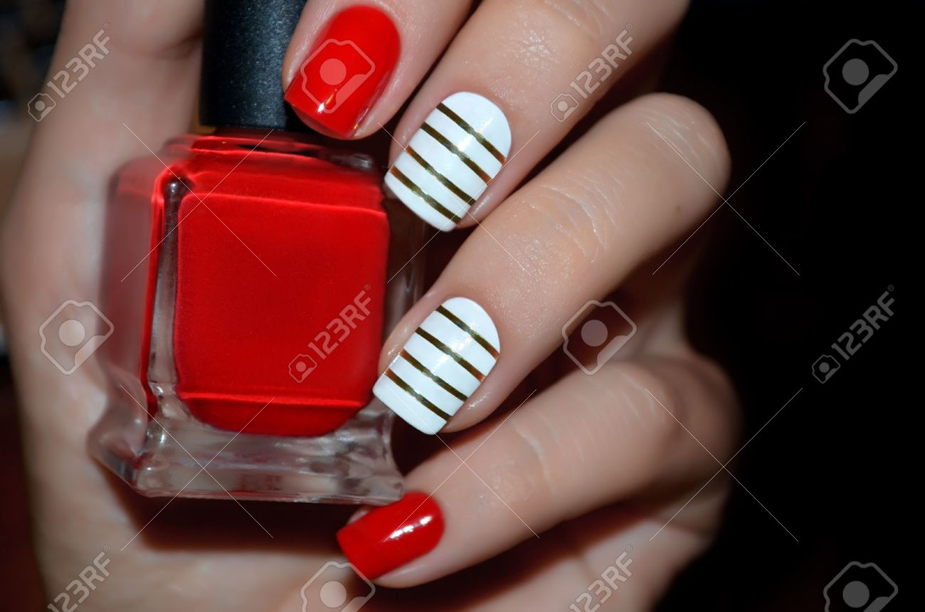 Red and white nail design with red polish bottle. Close up.