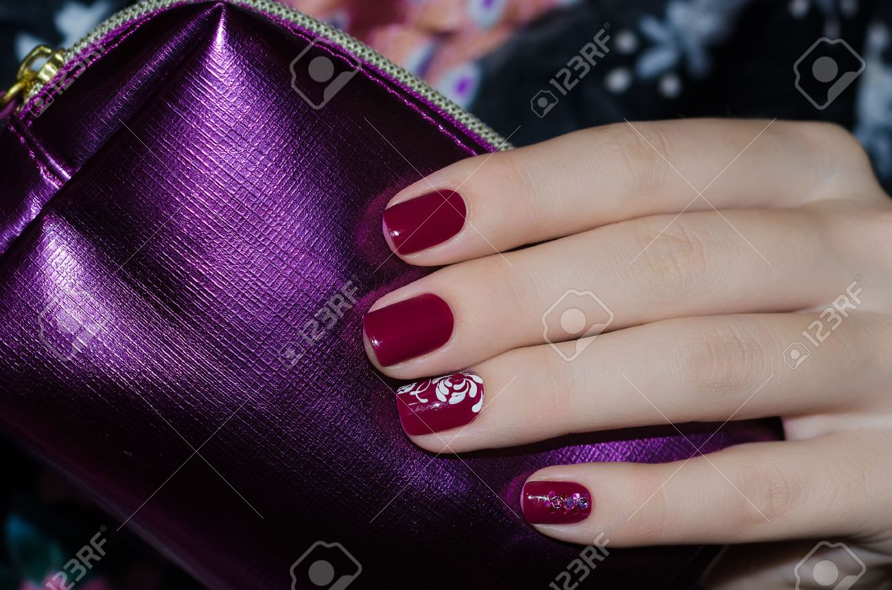 Woman Hand With Dark Red Nail Design And Purple Bag For Cosmetics ...