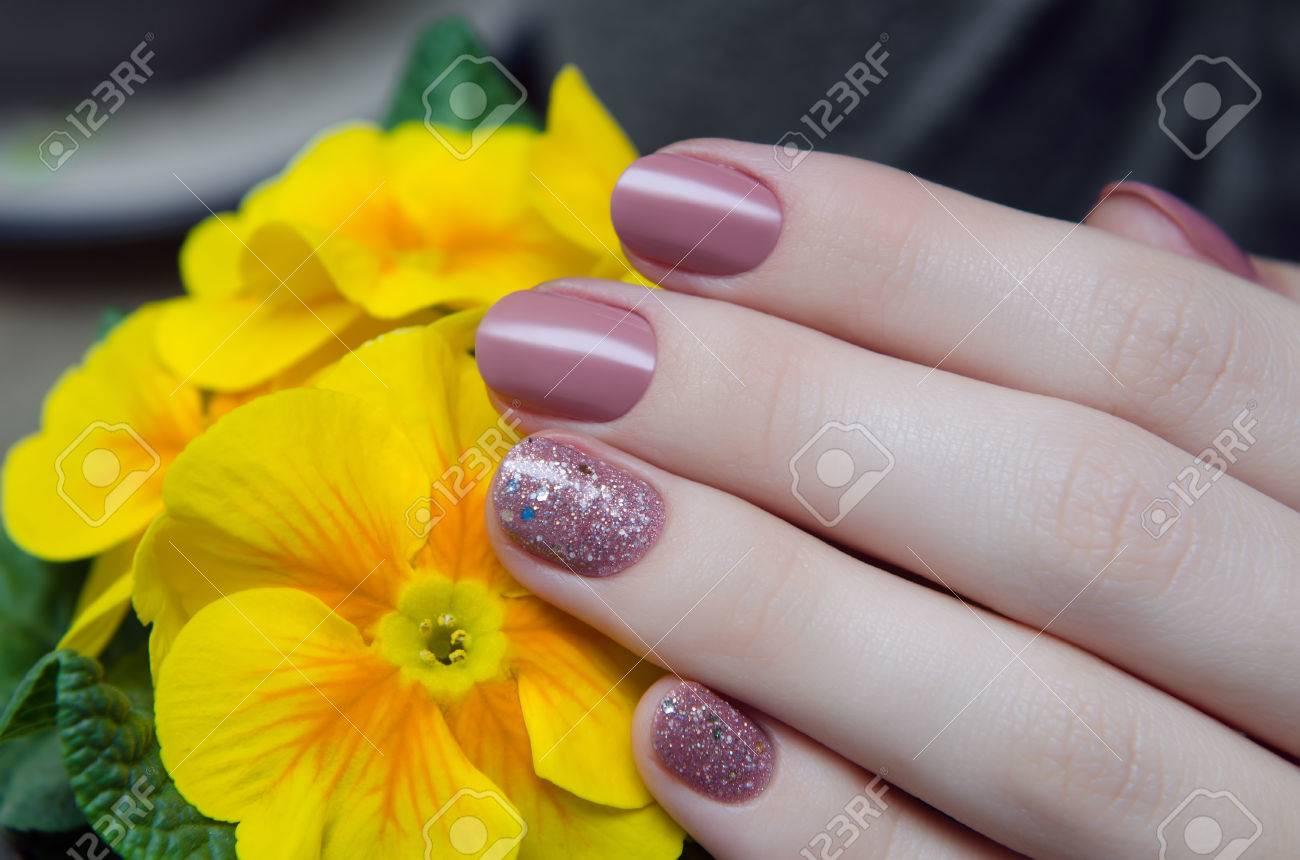 Hermosa Mano Femenina Con El Diseño De Uñas De Color Beige Cálido Y Flores De Color Amarillo Sobre Un Fondo