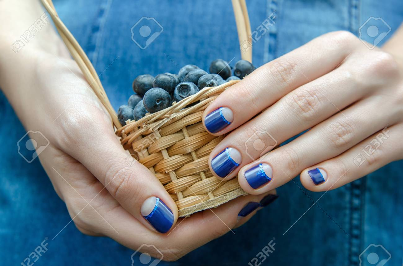 Female Hand With Blue Nail Design Holding A Small Basket With ...
