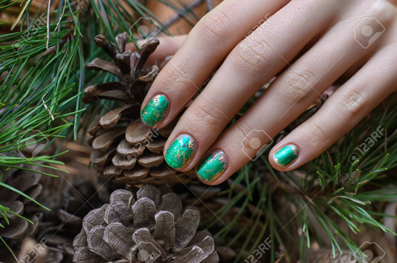 Female Hand With Green Foil Nail Design And Fir Cones On Background