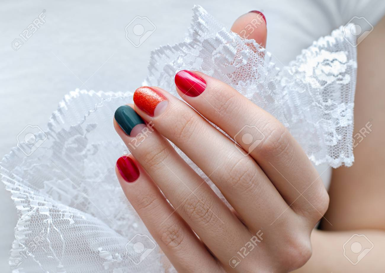 Female Hand With Red And Green Nail Design Holding Lace Stock Photo