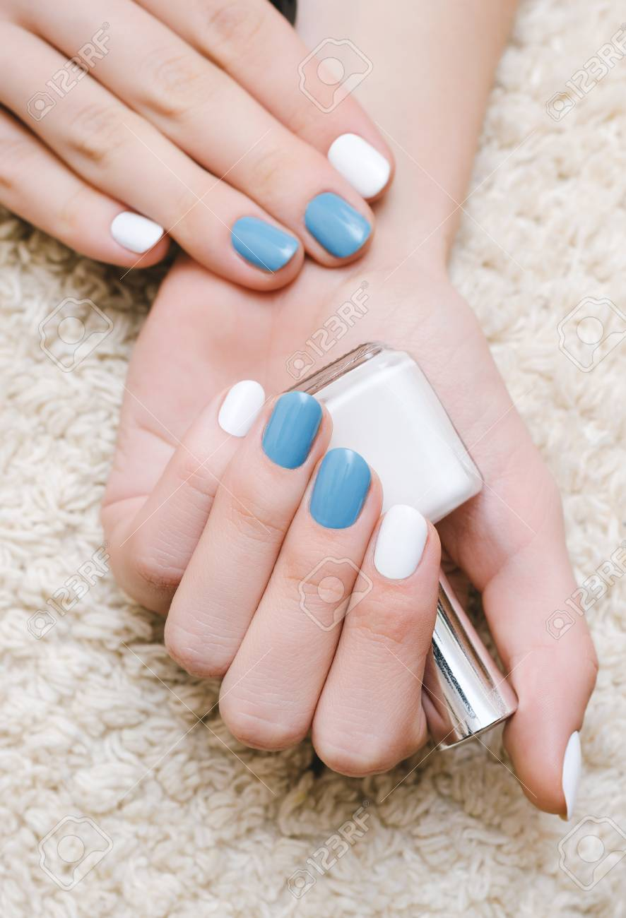 Beautiful Female Hand With White And Blue Nail Design Holding